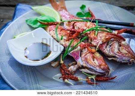 Two Red Mullet With Chili Pepper And Soja Sauce On Plate With Chopstick