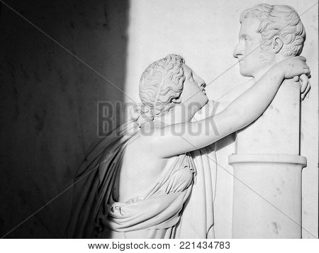 Bas relief of an ancient woman (roman or greek) hugs a man's bust. Really intense image