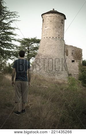 Man observing an old fortress in front of him, as a sort of defiance. Italian Castle, placed in Emilia Romagna region.