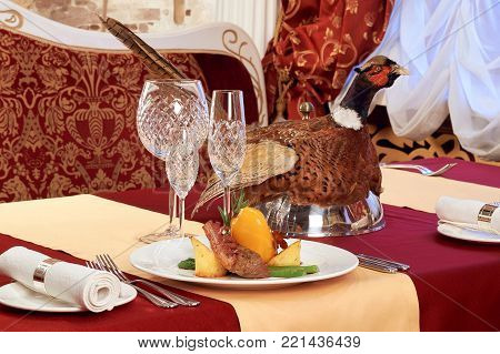 Decorated table with meat . The Cloche with bird pheasant on top.