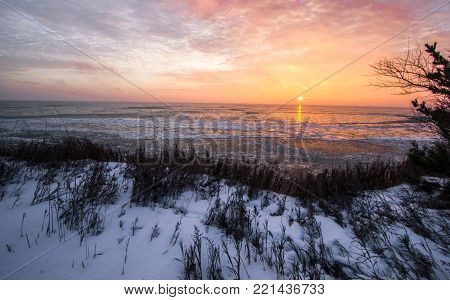 Frozen Great Lakes Sunrise. Scenic sunrise reflection over the icy Great Lakes horizon on the coast of Lake Huron from an overlook in Port Sanilac, Michigan.