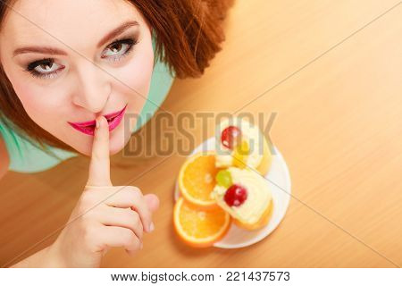 Woman eating delicious gourmet sweet cream cake cupcake and orange showing hand quiet sign gesture. Glutton girl having breakfast in secrecy. Appetite and gluttony concept.