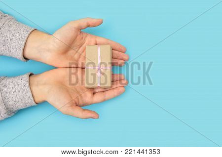 Male hands hold a small gift on a blue background. Women's hand goes to the man's hand on blue background.