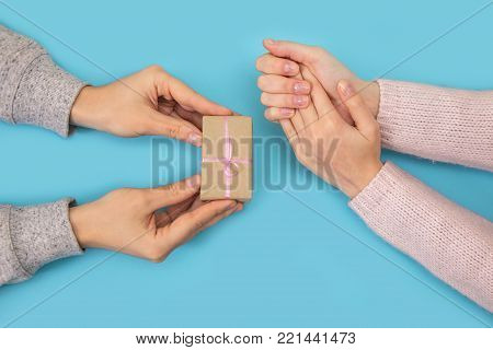 Women's hand goes to the man's hand on blue background. Men's hands give a small gift to a woman.
