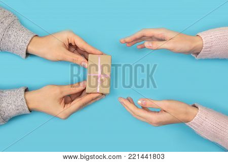 Men's hands give a small gift to a woman. Women's hand goes to the man's hand on blue background.