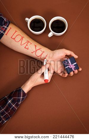 Pen to write a letter dear. a female hand writes I love you on a man's hand. On a brown background there are two cups of coffee and the man's hand is lying with a gift.