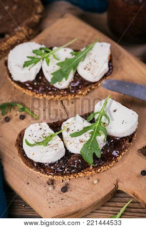 Bruschetta with fig jam, goat cheese and rucola on wooden plate. Sandwiches with cheese.