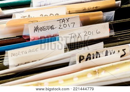 Scruffy and untidy file folders in file drawer sorted into tax years and mortgage documents