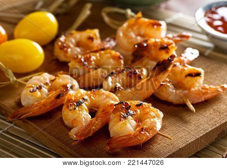Delicious grilled shrimp with sweet and sour chili sauce on a cedar plank.