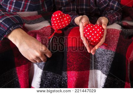 Love story. Romance. Couple in plaid shirts holding a red hearts hands. Two young lovers are warmed by a plaid and keep in hands red hearts.