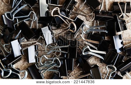 Pile of stationery bulldog clips on a beige carpet with space for text.