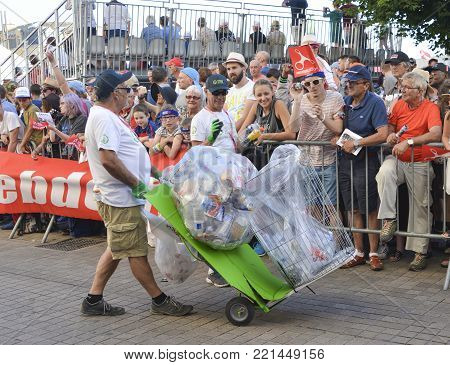 LE MANS, FRANCE - JUNE 16, 2017: Worker Man Collecting Garbage with cans and plastic on the street during the parade of pilots