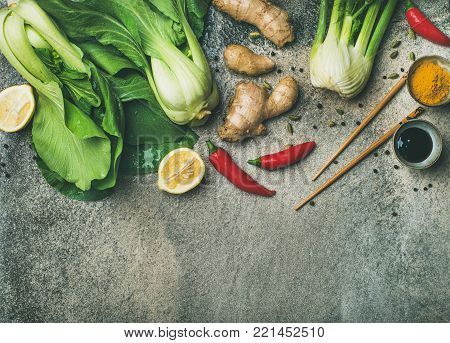 Asian cuisine ingredients over concrete background, top view, copy space. Flat-lay of vegetables, spices and sauces for cooking vietnamese, thai or chinese food. Clean eating, vegetarian diet concept