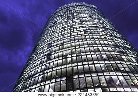 BERLIN, GERMANY - AUGUST 28, 2017; Towering building windows, high-rise modern office building from low angle with diminishing perspective rises into dark night sky.