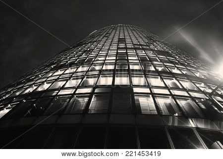 Berlin Germany - August 28, 2017; Tower of windows, high-rise modern office building from low angle with diminishing perspective risesinto dark sky.