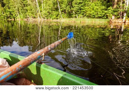 Closeup of oar paddle from row boat moving in water on green lake with ripples