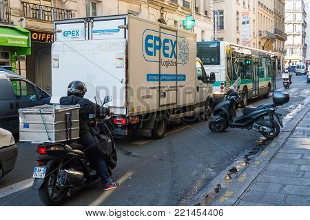 A man on a motorcycle from the delivery service on the street in Paris. France, Paris, October, 03, 2014.