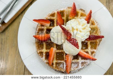 Belgian waffles topping with fresh strawberry, ice cream and whipped cream on with dish