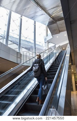 Young businesswoman with large black bag and mobile phone getting up the escalator during business trip in modern city.