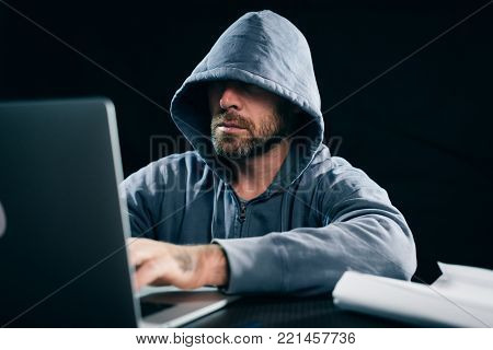 young guy hacker in a sweatshirt with a hood sits behind a laptop