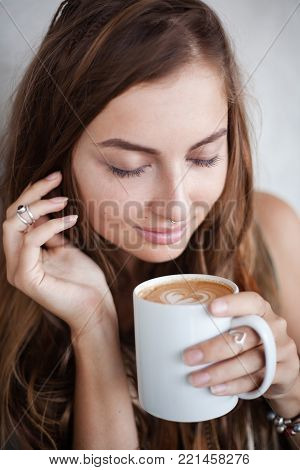 Close up portrait of girl with a mug of coffee with heart form foam. Her eyes are closed. Her face is close to the mug and she inhales the aroma of coffee. Her right hand holds her hair
