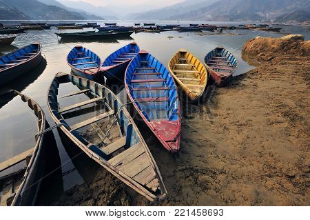 Wooden boat, red, blue and yellow on the earthy shore of a mountain lake.