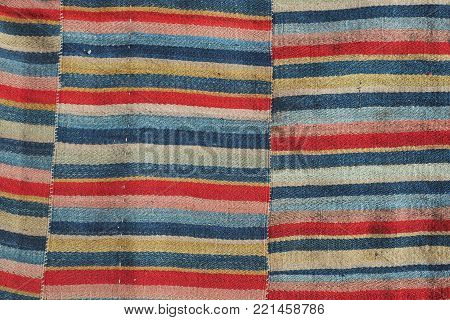 Abstract striped background of a handmade rug, striped thin stripes of red, blue, black and beige colors.