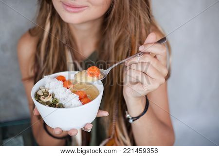 Close up photo of female hands with raw fruit bowl and spoon. There are nuts, seeds, coconut chips and fruits in her healthy breakfast. There is spoon with fruit ball in her left hand.