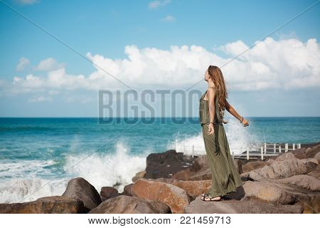 Young girl in long dress with long hair stands on a stone beach close to the sea waves. She spread her arms, turned her face to the ocean and closed her eyes. Blue waves and sky are on the background