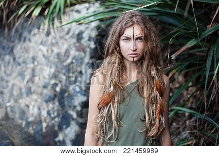 Art portrait of young pretty serious woman with black line and dots on her face. There are pigtails and bird feathers in her long brown hair. Stone wall is on background. She is looking at the camera