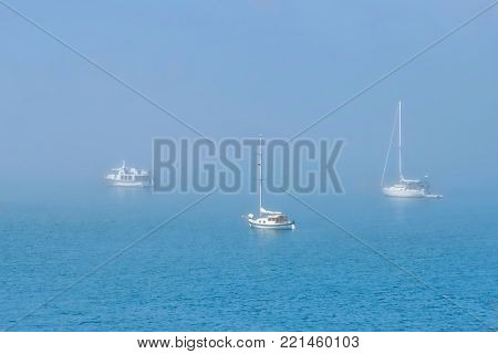 Boats in fog. Sailing boats moored on a misty harbor in Boston, Linconlnshire. United Kingdom.