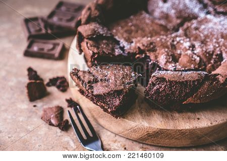 Close up of Chocolate cake on wooden tray with fork.