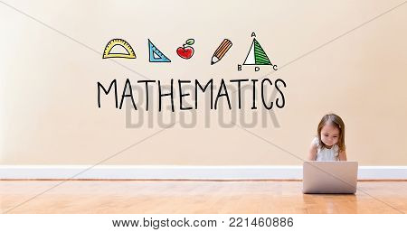 Mathematics text with little girl using a laptop computer on floor