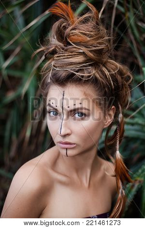 Portrait of attractive serios girl with painting on her face and high bunch of hair. There are black line and dots on her face. There are pigtails and feathers in her hair. She is looking at camera