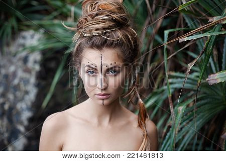 Portrait of beautiful girl with naked shoulders, art makeup and high bunch of hair. There are black line and dots on her face. There are pigtails and feathers in hair. She is looking at the camera.