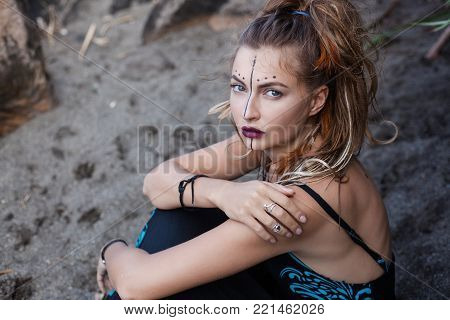 Portrait of beautiful girl with art makeup and high tail hair sitting on the sand. Her hairstyle has pigtails and feathers. There are black line and dots on her face and violet lips