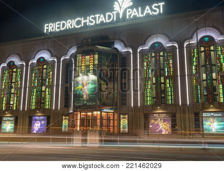 BERLIN, GERMANY - AUGUST 28, 2017; Friedrichstadt Palast retro style building at night, architecturally beautiful facade of famous theater with illuminated promotional signage.