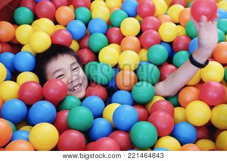 Asian boy having fun in ball pit, indoor play