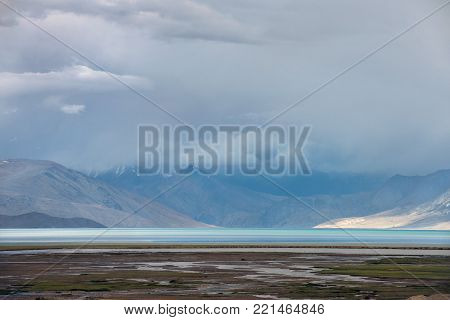 Morning mist on a mountain lake, a blue strip of water, into the background the mountains sink into the haze, to the foreground green meadows, Tibet, Himalayas.