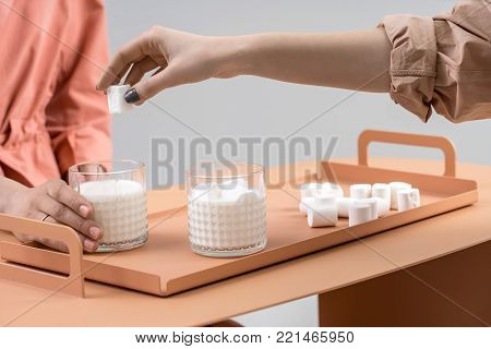 Two glasses with milk and marshmallows on the orange metal tray on the same table on a gray background in a studio. Couple of girls sitting near the table. One woman puts the marshmallow into glass.