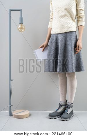 Charming girl stands next to the long lamp with edison bulb on the gray wall background in the studio. She wears a beige pullover, gray skirt, tights and boots. Woman holds a book in the right hand.