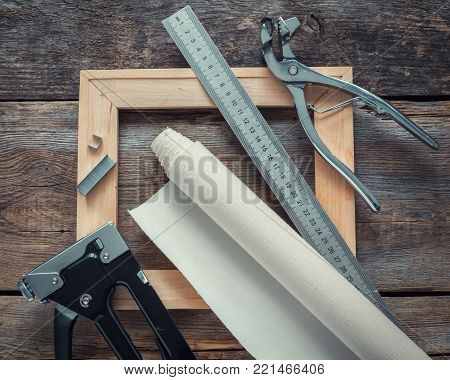 Artist canvas in roll, wooden stretcher bar, canvas stretcher pliers, staple gun and ruler for measuring on wooden background. Top view.
