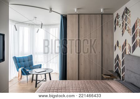 Bedroom in a modern style with a colorful wall with pine prints. There is a bed with a coverlet and pillows, nightstand with a book, wooden locker, blue armchair with a round table with a laptop, TV.