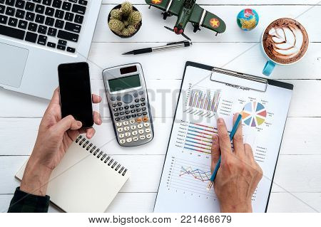 Businessman Discussing The Analysis Charts Or Graphs On Modern White Office Desk Table And Using Sma