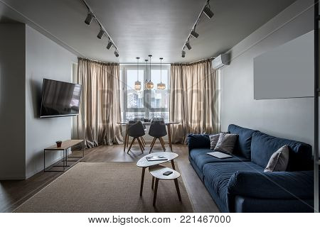 Stylish modern interior with white walls and a parquet with a carpet on the floor. There is a blue sofa with pillows, wooden tables, chairs, TV, stand with plant, window with curtains, hanging lamps.