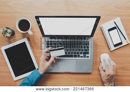 Hipster man hands holding laptop and using credit card for online shopping.Online shopping concept.