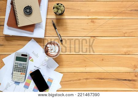 Office desk table with analysis chart or graph, pen, cup of coffee and calculator. Top view with copy space.Working desk table concept.