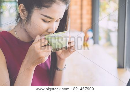 Young woman drinking hot green tea matcha latte at cafe.