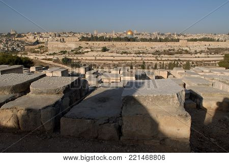 Graves in the Jewish cemetery on the Mount of Olives in Jerusalem, huge stone tombstones, in the background old Jerusalem, Israel.