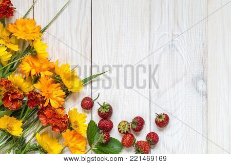 Calendulae and marigolds on a light wooden background.